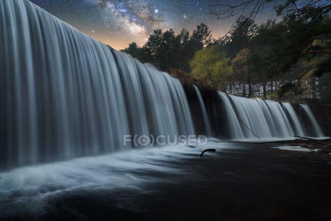 Hermosa cascada rocosa de gran alcance y corriente de agua con cielo estrellado noche colorida en el fondo - foto de stock
