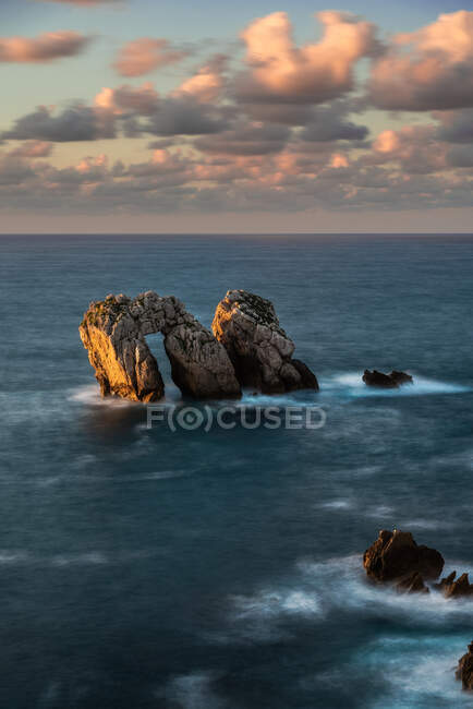 Dall'alto pittoresco scenario di rocce grezze tra il mare blu calmo sotto il cielo colorato della sera con raggi di sole che sfondano le nuvole durante il crepuscolo Costa Brava, Spagna — Foto stock