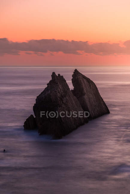 From above picturesque scenery of rough rocks among calm blue sea under colorful evening sky with sun beams breaking through clouds during twilight Costa Brava, Spain — Stock Photo