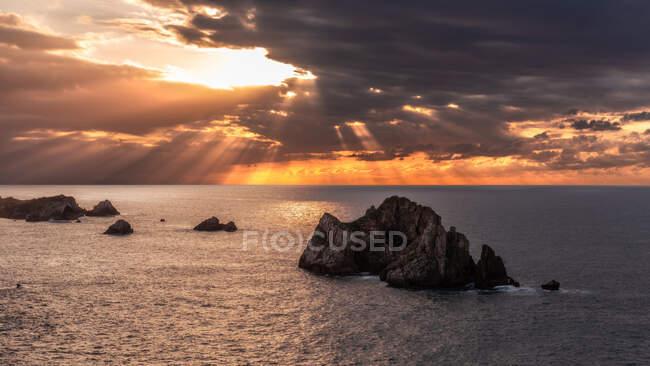 Do cenário acima pitoresco de rochas ásperas entre o mar azul calmo sob o céu colorido da noite com raios do sol que quebram através das nuvens durante o crepúsculo Costa Brava, Spain — Fotografia de Stock
