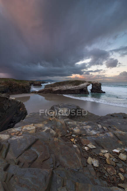 Rough rocks on shore of calm ocean under grey clouds on bright sky — Stock Photo