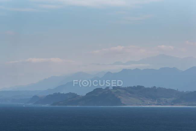 Surface calme de l'océan et falaise rugueuse sous un brouillard épais avec un soleil éclatant dans un ciel nuageux — Photo de stock