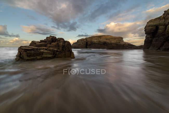 Big rocky formations on sandy empty beach of ocean with cloudy bright evening sky on background — Stock Photo