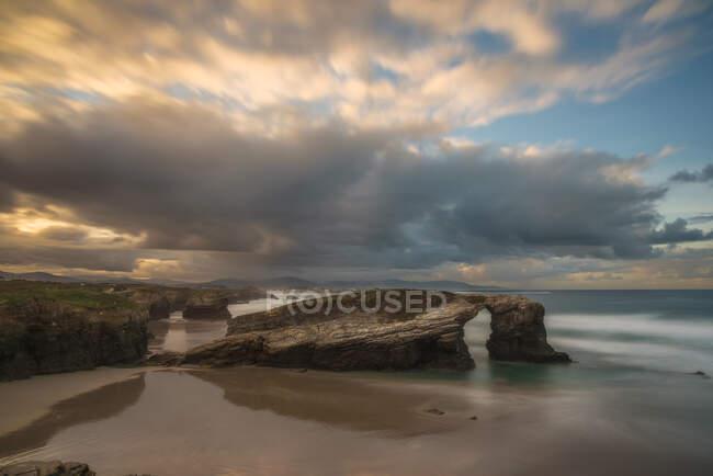 Grandes formaciones rocosas en la playa de arena vacía del océano con el cielo nublado brillante de la noche en el fondo - foto de stock