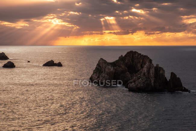 D'en haut décor pittoresque de rochers rugueux au milieu d'une mer bleue calme sous un ciel nocturne coloré avec des rayons de soleil brisant les nuages au crépuscule Costa Brava, Espagne — Photo de stock