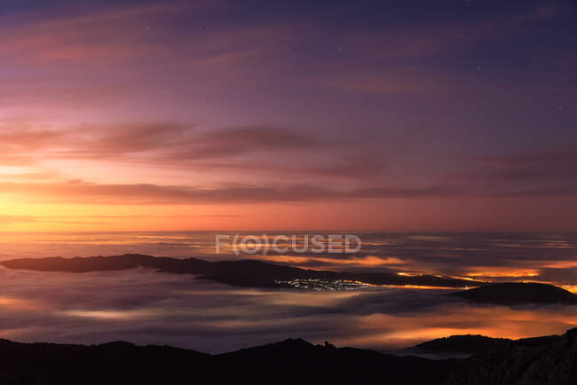 Aerial view of modern city and mountains covered with tick clouds under colorful sky during sunrise — Stock Photo