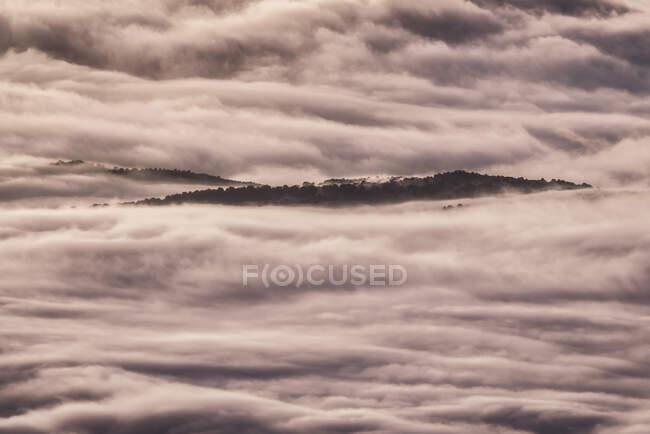 D'en haut des sommets noirs des montagnes puissantes parmi les nuages épais blancs doux — Photo de stock