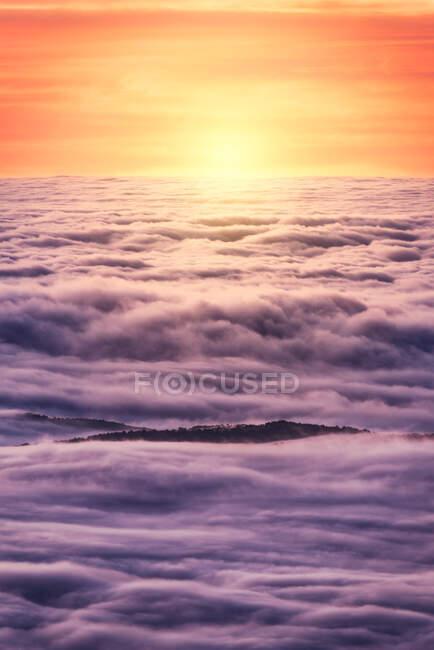 D'en haut des sommets noirs des montagnes puissantes parmi les nuages épais blancs doux au lever du soleil — Photo de stock