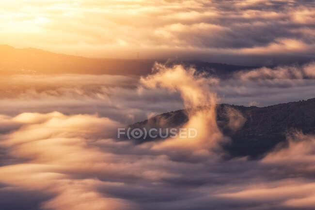 De arriba de los picos negros de las montañas potentes entre las nubes blancas suaves gordas al amanecer - foto de stock