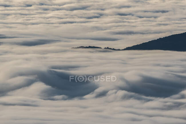 From above of black peaks of powerful mountains among soft white thick clouds — Stock Photo