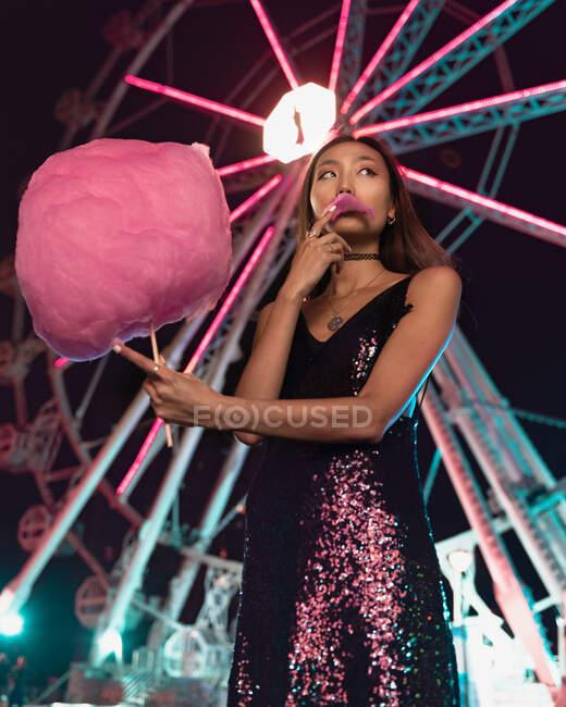 Desde abajo señora asiática en vestido brillante comiendo algodón rosa de azúcar y mirando hacia otro lado, mientras que de pie cerca de la rueda de la fortuna en la noche en el recinto ferial - foto de stock