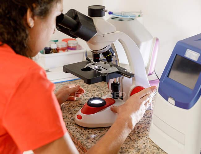 Vue arrière d'un médecin féminin méconnaissable regardant à travers un microscope moderne tout en travaillant dans une clinique moderne — Photo de stock