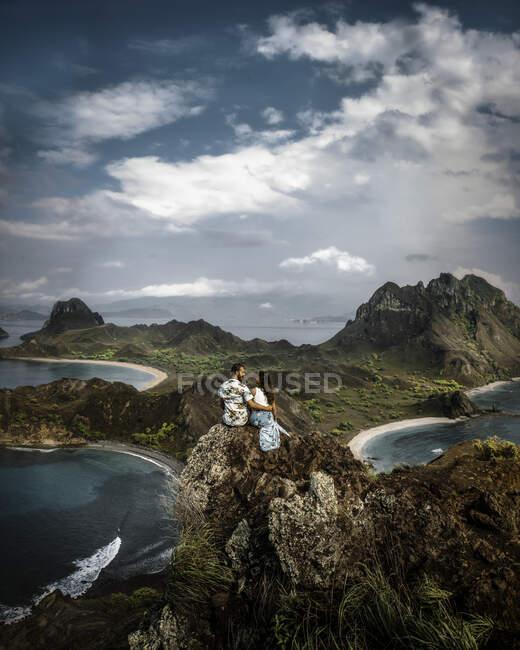 Vista laterale di spensierata giovane coppia in vacanza in leggero abbigliamento casual in piedi sulla cima di ruvida scogliera e guardarsi a vicenda con paesaggio mozzafiato sullo sfondo in Indonesia — Foto stock