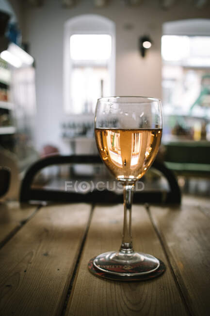 Glass of wine placed on wooden plank table against daylight from windows in rustic restaurant — Stock Photo