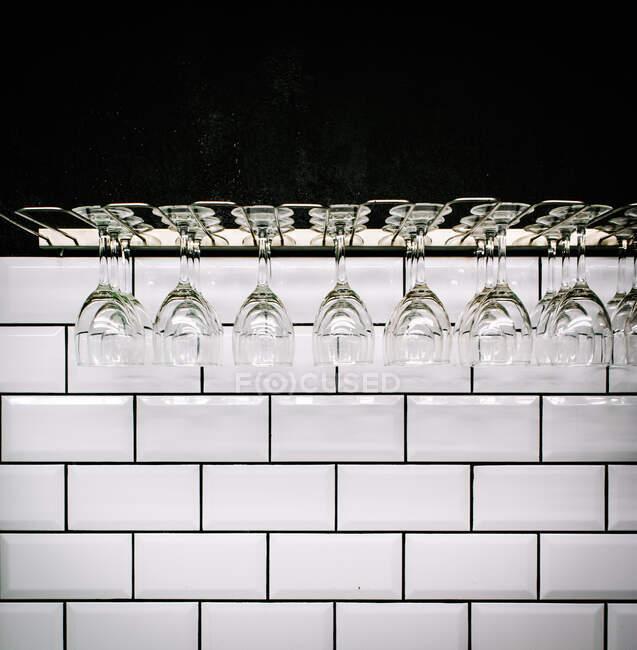 Fila de limpias gafas de vino pulidas colgando contra la pared de baldosas blancas en barra vintage - foto de stock