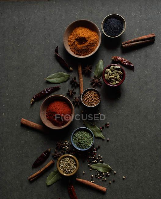 Composición de vista superior con diferentes tipos de especias aromáticas naturales colocadas sobre fondo gris oscuro - foto de stock