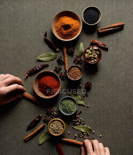 Vista superior de la cosecha irreconocible persona sosteniendo palos de canela cerca de la olla con pimentón rojo en polvo sobre la mesa gris con conjunto de especias aromáticas surtidos - foto de stock
