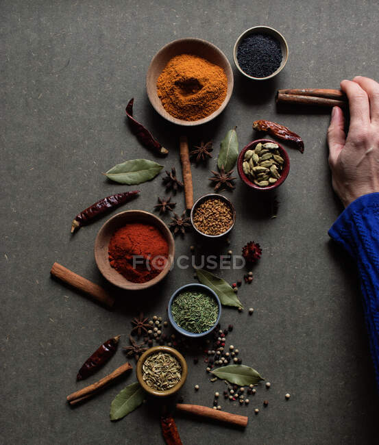 Top view of crop unrecognizable person holding cinnamon sticks near pot with red paprika powder over gray table with set of assorted aromatic spices — Stock Photo