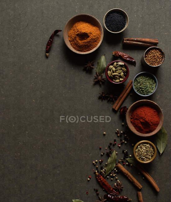 Composition vue de dessus avec différents types d'épices aromatiques naturelles placées sur fond gris foncé — Photo de stock