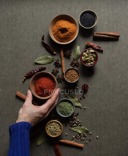 Top view of crop unrecognizable person holding pot with red paprika powder over gray table with set of assorted aromatic spices — Stock Photo