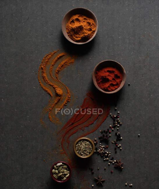 Composition vue de dessus avec différents types d'épices aromatiques naturelles placées sur fond gris foncé avec des épices en poudre déversées sur la surface — Photo de stock