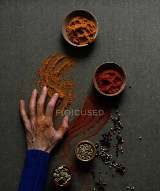 Vista superior de la cosecha irreconocible persona tocando mesa con pimentón derramado y polvos de canela - foto de stock