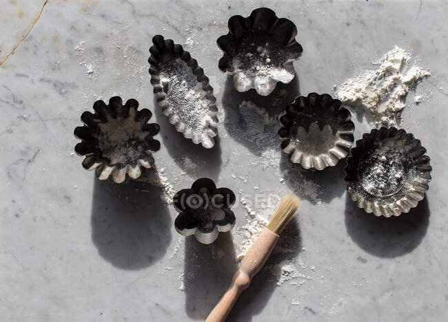 Top view of various metal baking molds and small kitchen brush on marble table sprinkled with white flour — Stock Photo