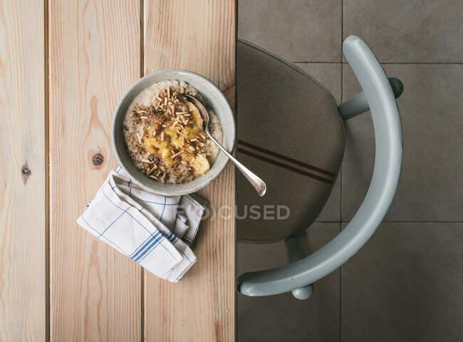 Vista superior del bowl con gachas frescas servidas con rodajas de plátano y cuchara sobre mesa de madera - foto de stock