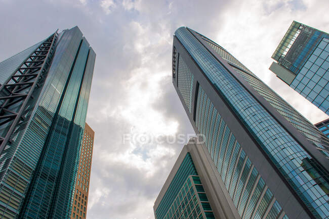 From below of contemporary skyscrapers with glass mirrored walls against cloudy sky with sunlight in Japan — Stock Photo