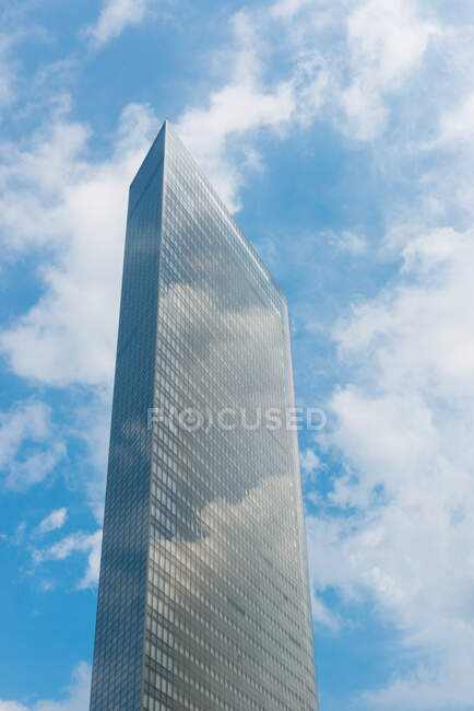 From below of contemporary city tower against blue cloudy sky reflected in glass wall in sunny day in Japan — Stock Photo