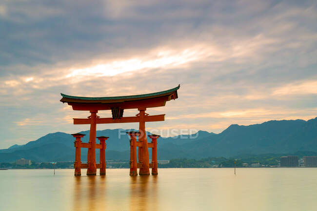 Picturesque view of famous floating gate of ancient Itsukushima Shrine in Japan under cloudy sky with sunlight and foggy mountains in background — Stock Photo