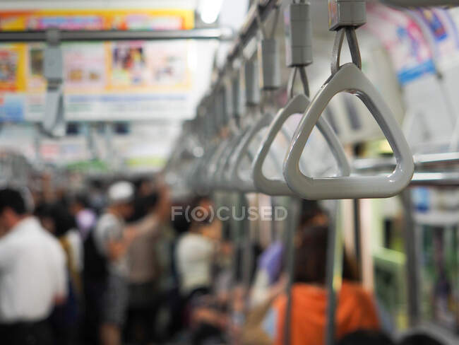 Handles for standing passengers in blurred contemporary subway train with commuters in Japan — Stock Photo