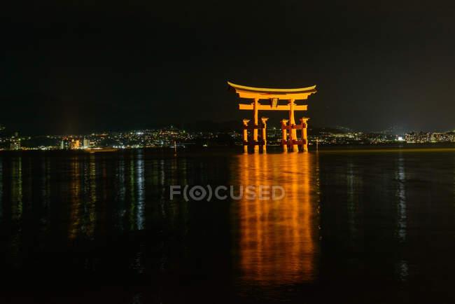 Vue imprenable de la porte flottante lumineuse de l'ancien sanctuaire au Japon reflétée dans l'eau calme dans la nuit avec un ciel sombre en arrière-plan — Photo de stock