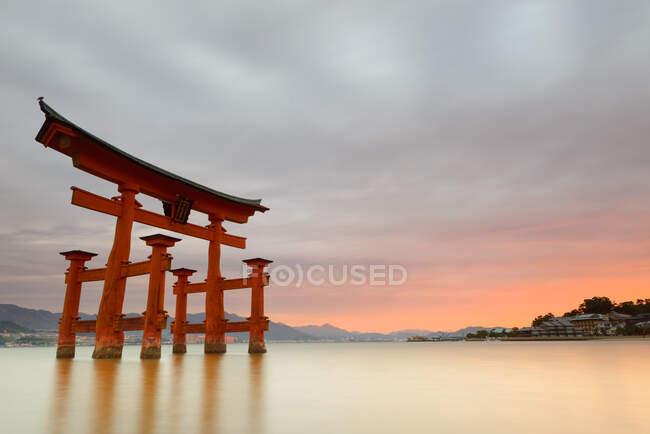 Magnifique paysage de coucher de soleil tranquille avec célèbre sanctuaire flottant sur l'eau calme avec un beau ciel nuageux en soirée d'été au Japon — Photo de stock
