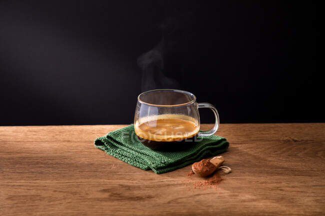 Glass cup of aromatic hot black coffee on green napkin placed with spoon of ground cinnamon on wooden table with black background — Stock Photo