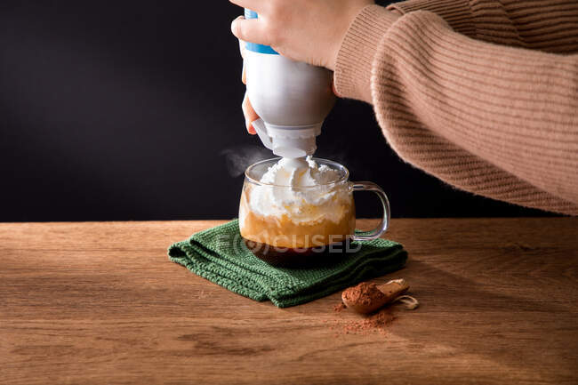 Side view of crop female preparing delicious drink and pouring whipped cream into cup with hot black coffee with cinnamon — Stock Photo