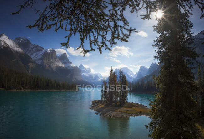 Amazing Canadian landscape with tiny island with spruce trees in beautiful calm lake with turquoise water surrounded by majestic rocky mountains covered with snow framed by branches of coniferous trees in sunny day — Stock Photo