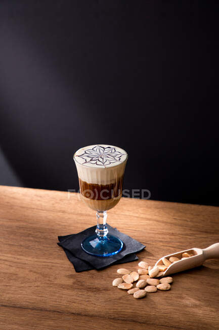 From above of appetizing cold coffee drink with cream and almonds served on glass on wooden table with black background — Stock Photo