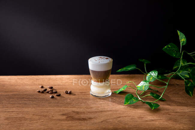 Delicious coffee drink with cream and coffee grains on table — Stock Photo