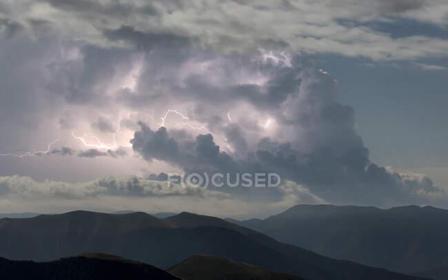 Громовые облака с молнией над темным скалистым горным хребтом — стоковое фото