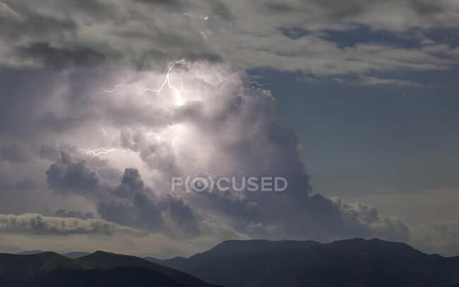 Nuages de tonnerre avec éclair sur ciel bleu au-dessus d'une chaîne de montagnes rocheuses sombres — Photo de stock
