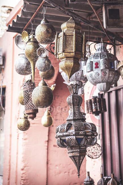 Conjunto de faroles árabes tradicionales surtidos colgando en el techo fuera del edificio de mala calidad - foto de stock