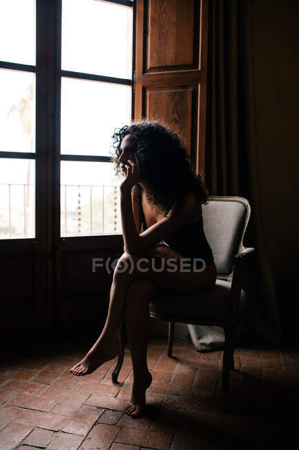 Vista lateral de mujer joven sensual de cuerpo completo en ropa interior sentada en silla cómoda y mirando por la ventana en habitación oscura vintage - foto de stock