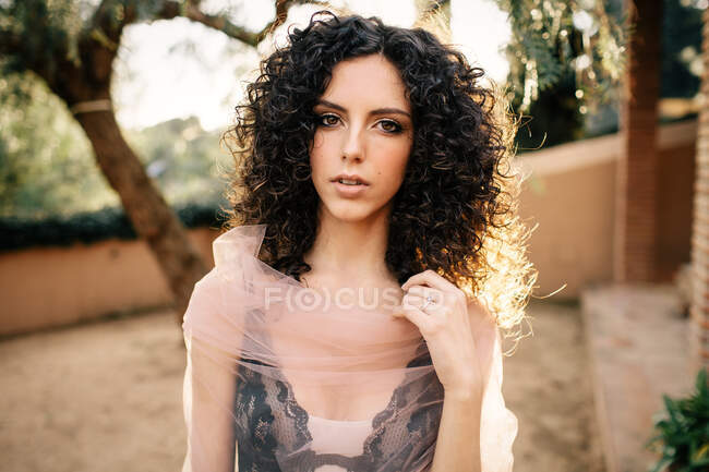 Young beautiful woman in translucent trendy garment standing on path in park looking at camera — Stock Photo