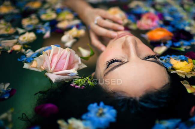 Desde arriba atractiva cara femenina tocando mientras está acostado en la bañera con agua tibia y varias flores de colores - foto de stock