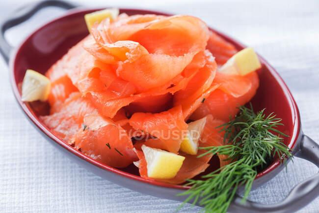 Сверху ломтики свежего лосося с кусочками лимона и ароматного укропа на тарелке на столе ресторана — стоковое фото