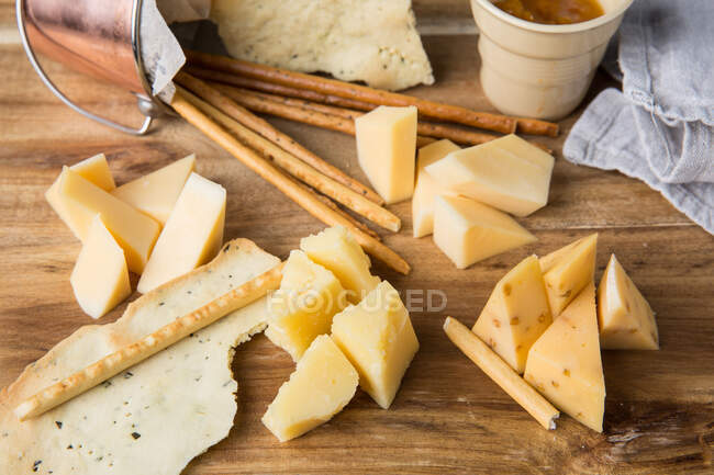 Top view of small bowl with spicy sauce and pieces of cheese placed on wooden table near crispy salty sticks and tortilla chips in cafe — Stock Photo