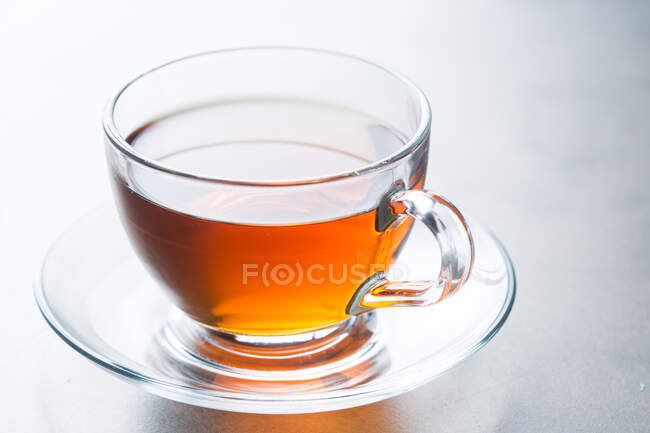 Closeup glass cup of aromatic hot tea placed on saucer on table in cafeteria — Stock Photo