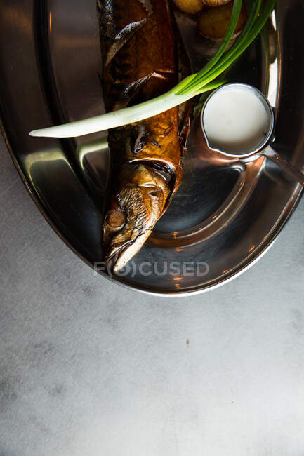 Top view of yummy roasted fish and potatoes served with ripe scallion and cream sauce on metal plate in restaurant — Stock Photo