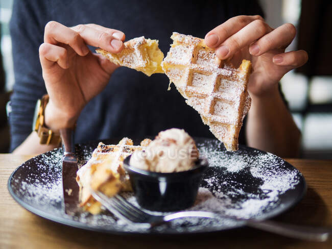 Anonymous person breaking off piece of soft waffle over plate with tasty ice cream while sitting at table in restaurant — Stock Photo